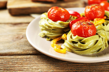Tasty green pasta with pepper, and tomatoes