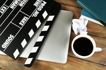 Movie clapper with laptop and cup of coffee on wooden