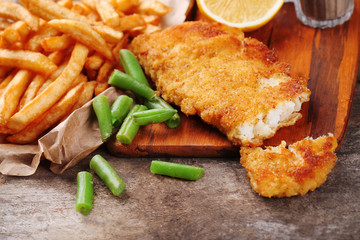 Breaded fried fish fillet and potatoes with asparagus and lemon