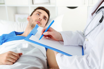 Doctor filling medical report for her patient close up