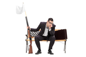 Businessman holding rifle with white flag on it