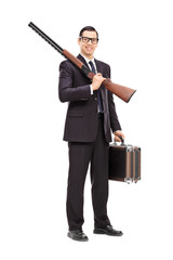 Businessman holding a rifle and a briefcase