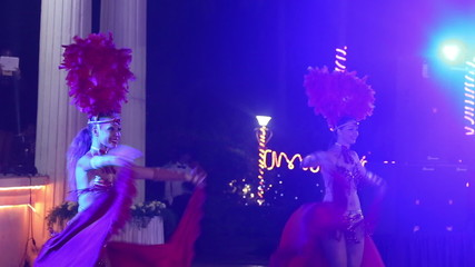 two girls wearing red theatrical costumes are dancing