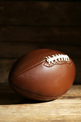 American football on wooden table, close up