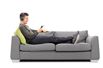 Young guy lying on sofa and listening to music