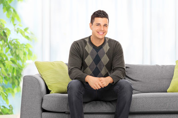 Young man posing seated on a sofa at home