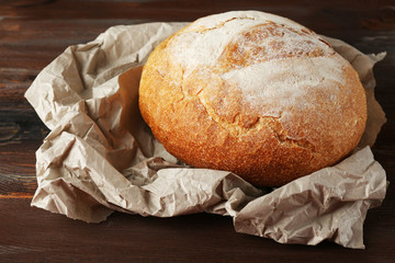 Fresh bread on paper on wooden background