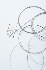 Full set of electric guitar strings on a white surface