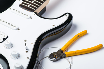 Black electric guitar with nippers and strings