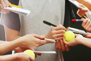 Sportsman signing autograph on tennis ball on dark background