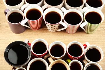 Many cups of coffee on wooden table background, closeup view