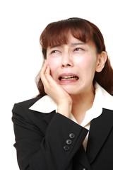 虫歯の痛みに苦しむビジネスウーマン