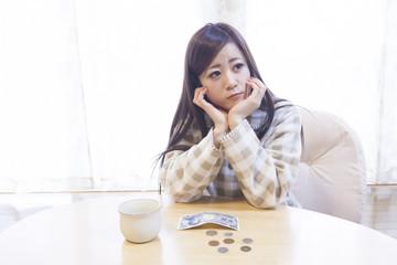 机の上にお金を広げる女性