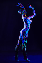 Graceful nude dancer with glowing body art