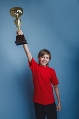 European- looking  boy of ten years cup, sports, award on a gray