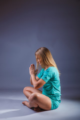 girl blonde European appearance in a blue tracksuit meditates on