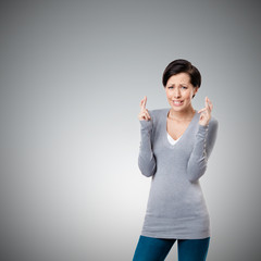 Worrid woman shows crossed fingers, isolated