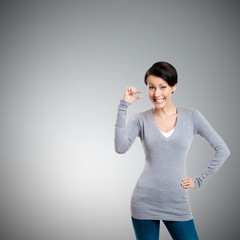Attractive woman gestures small amount, isolated