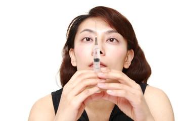覚醒剤の注射器を準備する女性