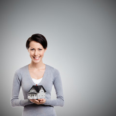Young woman hands small toy house in front of herself, isolated