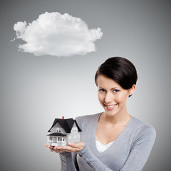 Young woman hands small toy house, isolated on grey