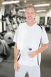 Mature Man Holding Bottle Of Water At Gym