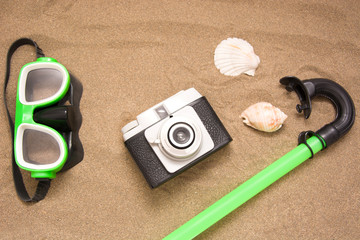 snorkel, old camera and shell on sand