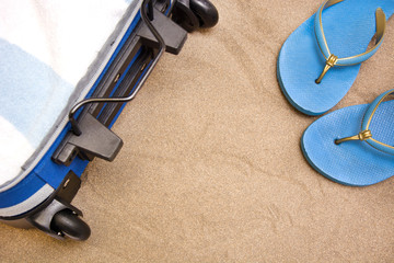 Suitcase and summer shoes on sand