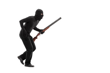Stealthy criminal with a mask and a rifle walking