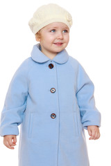 Little girl in blue autumn coat and a white cap.
