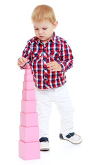 very small boy collects Red Pyramid in the Montessori classroo
