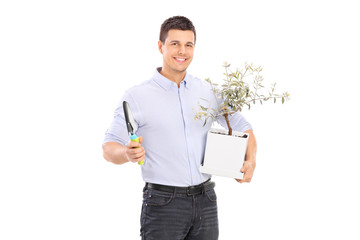 Young man holding an olive tree plant and a spade