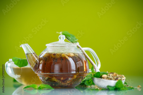 canvas print picture green tea in a glass pot on a green background