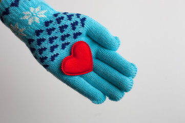 Read heart in hand in warm glove for Valentine's Day