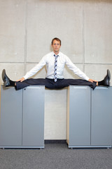 flexible business man in  straddle, split position on cabinets