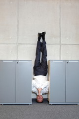 business man standing on his head between cabinets in office