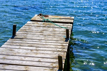Wooden jetty in water at the beach in the summer..