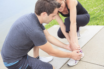 Injury - sports woman with twisted sprained getting help from ma