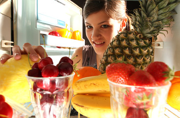 Frau geift in Kühlschrank