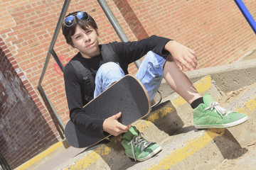 A Teenager boy portrait with skateboard against brick wall with