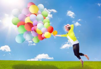 reife vitale frau springt mit ballons