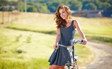 Sexy woman with vintage bike in a country road.