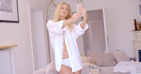Sexy Blond Woman in White Taking Selfie