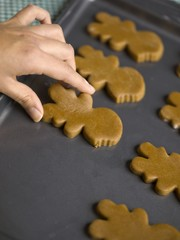 hand placing cookies on tray