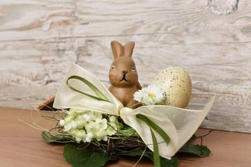 Osterhase mit Osterei im Nest vor Holz Hintergrund als Ostergruß