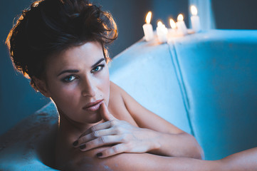Woman in bath tub with candles