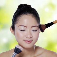 Asian girl apply makeup on bokeh background