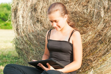 Young girl with  device siting close  to haystack