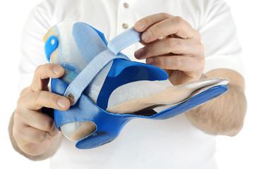 Orthopäde zeigt Orthese für Fuß