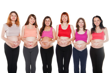 Group of happy pregnant women touching their bellies. Maternity